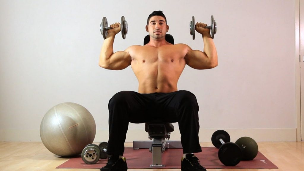 A man trains shoulder muscles doing overhead dumbbell press