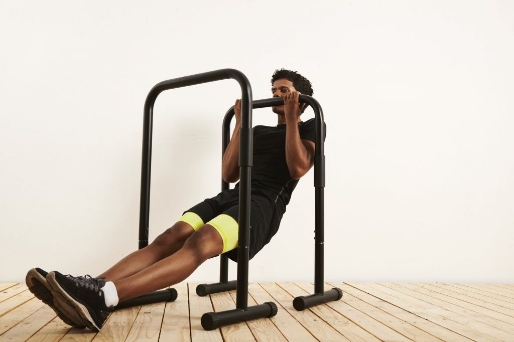 A guy in black and yellow doing Bodyweight Rows exercise