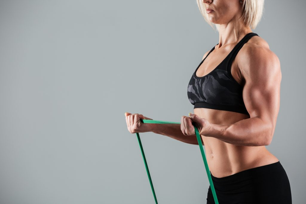 Female bodybuilder stretching with a resistance band