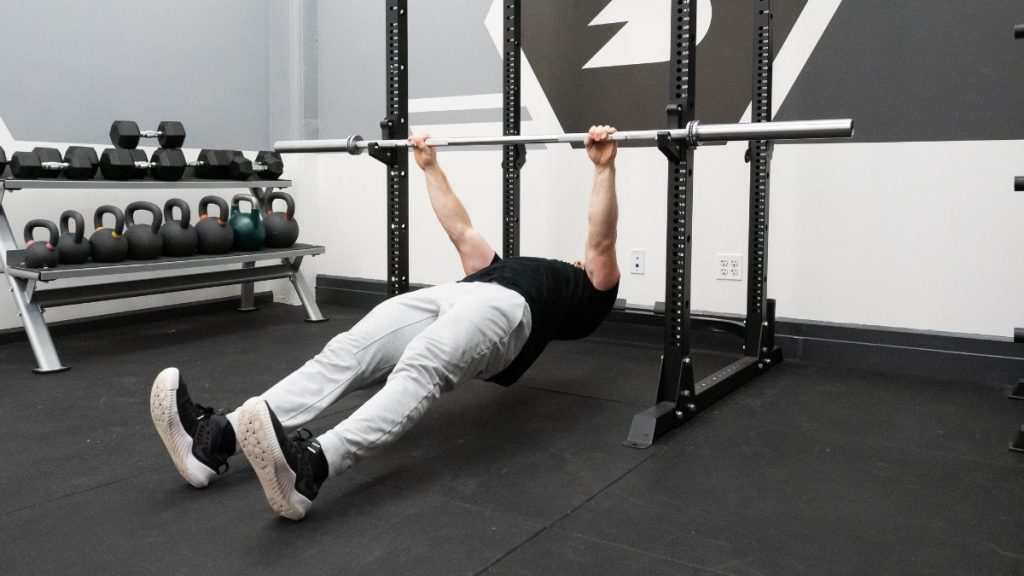 A guy in jeans doing inverted rows exercise